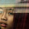 Face in the window, Mekong Ferry - There was a distant caution on this child's face, peering out at me from the back seat of a van being hauled across the Mekong River on a ferry boat.